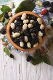 White and black mulberries in a wooden bowl vertical top view Stock Image