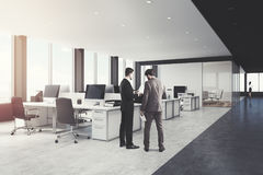 White and black open space office side, men. Side view of two men in a white and black open space office interior with rows of computer tables with desktops Stock Photos