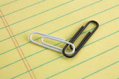 White and Black Paper Cliips. Black and white paper clips connected on a legal pad of paper Royalty Free Stock Photography