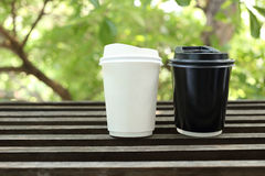 White and black paper coffee cup on wooden with green leaves bac Stock Photos