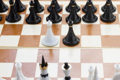 White and black pawn in front of black chess Stock Photo