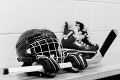 White and black photo of girl`s hockey gear: helmet, gloves, sticks, skates with laces. All equipment are on the bench royalty free stock photo