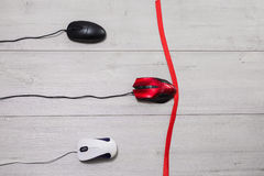White and black, and red computer mouse on a white wooden background. Stock Images