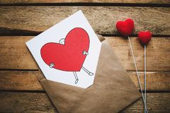 White, Black, and Red Person Carrying Heart Illustration in Brown Envelope stock photos