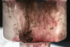 White, black, red pink ink in water in glass container. Sunshine lighting. Dynamic movement of paint in the water.  proc. White, black, red pink ink in water in Royalty Free Stock Image