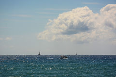 White and black sailboat in the Mediterranean sea, beautiful cumulus clouds Royalty Free Stock Photos