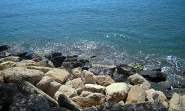 White and black sea rocks on the seaside and glitter shiny water Stock Images