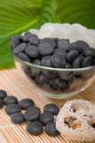 White and black stones. Lay in a vase on a mat with a green leaf Stock Image