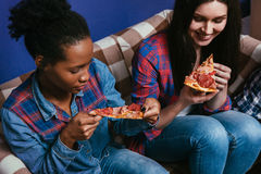 White and black woman enjoy eating pizza, closeup Royalty Free Stock Image