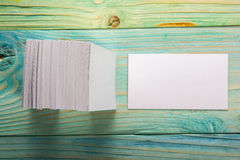 White blank business visit card, gift, ticket, pass, present close up on blurred blue background. Copy space Royalty Free Stock Photos
