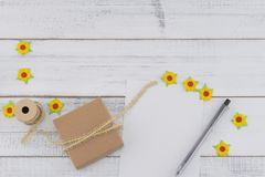 White blank card, brown gift box and pen decorate with yellow paper flowers and brown rope. On white wood back ground with copy space Royalty Free Stock Photos