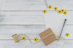 White blank card, brown gift box and pen decorate with yellow paper flowers. And brown rope on white wood background Stock Photos