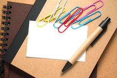 White blank card with paper clips and pen Royalty Free Stock Photo
