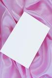 White blank card on pink satin Stock Image