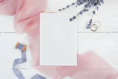 White blank card ribbon with two wedding rings on a background of pink fabric with lavender flowers on a white. Background. Mockup with envelope and blank card Royalty Free Stock Photography