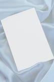 White blank card on white satin royalty free stock image