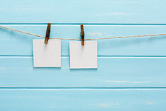 White blank cards on rope, blue wooden background Royalty Free Stock Photo