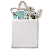 White blank cotton eco tote bag, design mockup. White blank cotton eco tote bag with flowers and notebook, design mockup royalty free stock photo