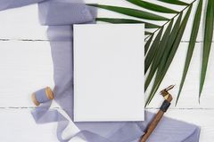 White blank greeting card ribbon on with space for your text of blue fabric with palm leaf and calligraphic pen on a. White background. Mockup with envelope and stock image