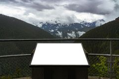 White blank information billboard viewpoint in the mountains on a moody and cloudy day. Outdoors concept advertisment or royalty free stock photo