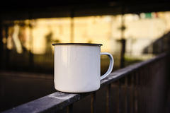 White and blank metal tea cup on the rails. Blurred background. 3d rendering Stock Photos