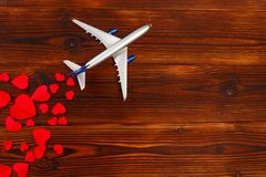White blank model of passenger airplane on shapes of heart over wooden background. Image royalty free stock images