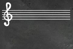 White blank musical five lines staff with violin cleff on it on black chalkboard. Horizontal with copy space for text or design stock illustration
