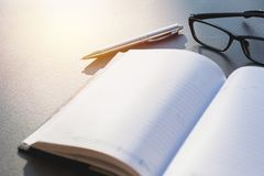 White blank notebook, textbook with glasses and pen on table wit. H copy space Royalty Free Stock Image