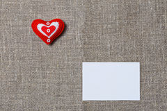 White blank notecard and handmade heart. White blank notecard and red handmade heart on textile background Stock Image