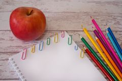 White blank page copyspace and colorful pencils and red apple on a wooden desk. Concept of begining of the school year, back to royalty free stock images