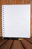 White blank page with row and classic pen. White blank page with row,classic pen on tile wall and wood floor stock photography