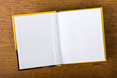 White blank pages of an open book. View from directly above, placed on a wooden table royalty free stock image