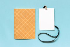 White blank paper badge mockup with black string and notebook on blue background. Copy space for text. Template Royalty Free Stock Image