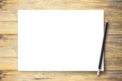 White blank paper or notepad with pencil on brown wood table background stock image