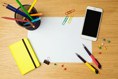 White blank paper page with smartphone and pencils on modern desk. Stock Images