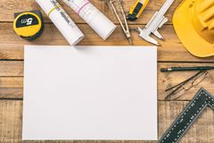 White blank paper, project construction blueprints and engineering tools on wooden desk, copy space royalty free stock image