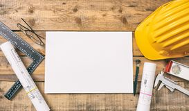 White blank paper, project construction blueprints and engineering tools on wooden desk, copy space royalty free stock photo