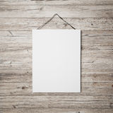 White blank poster hanging on leather belt on wood background Royalty Free Stock Photos