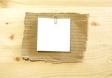 White blank on ripped cardboard on wooden Royalty Free Stock Image