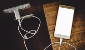 White blank screen smartphone charging Royalty Free Stock Images