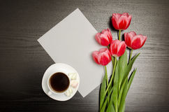 White blank sheet of paper, pink tulips and a mug of coffee. Black table. top view Stock Image