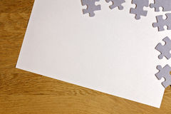 White blank sheet of paper with puzzle pieces on wooden background. Top view. Copy space for text Stock Photos