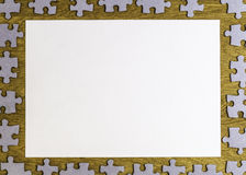 White blank sheet of paper surrounded by puzzle pieces on wooden background. Top view. Copy space for text Royalty Free Stock Photos
