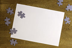 White blank sheet of paper surrounded by puzzle pieces on wooden background. Top view. Copy space for text Stock Photo