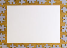 White blank sheet of paper surrounded by puzzle pieces on wooden background. Top view. Copy space for text Royalty Free Stock Image