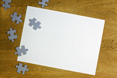 White blank sheet of paper surrounded by puzzle pieces on wooden background. Top view. Copy space for text Stock Images