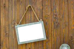 White blank space board with rope on wooden door of a coffee sho Royalty Free Stock Photography