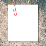 White blank space and red paper clip on stone Stock Images