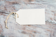 White blank tag with string on gray wooden background Stock Image