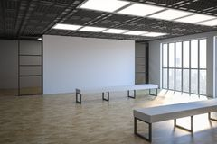 White blank wall in gallery hall. Side view on loft style empty exhibition white blank banner in gallery with white benches on parquet floor and floor-to-ceiling Royalty Free Stock Photography